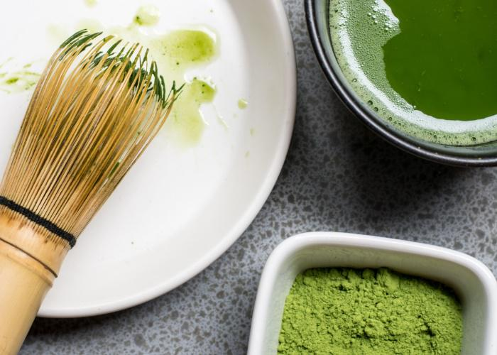 Bowl of freshly frothed matcha tea next to a chasen tea whisk