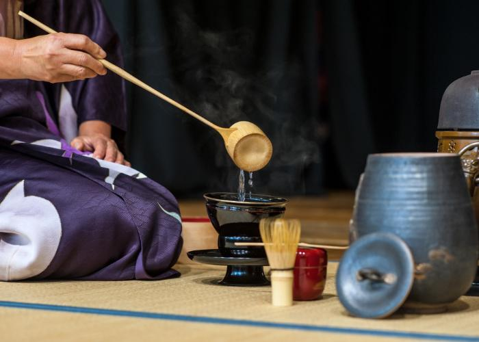 Host ladles hot water into a tea bowl during a Japanese tea ceremony