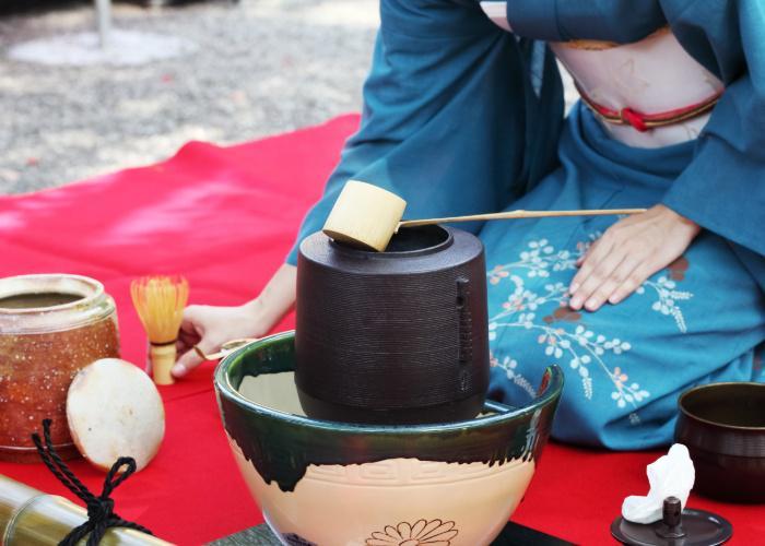 Woman wearing blue Japanese kimono hosts a tea ceremony outside