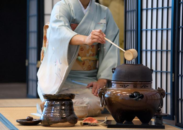 Woman in kimono gives a Japanese tea ceremony demonstration